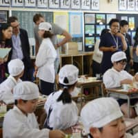 Journalists from Group of 20 countries and regions observe children eating prepared lunches at an elementary school in Osaka in May, as part of a program of events leading up to the summit in June. | KYODO