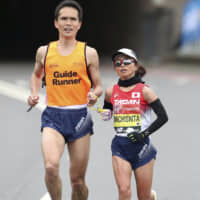 Misato Michishita runs with a guide during the women's pararace in the London Marathon on April 28. | REUTERS
