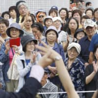 Voters listen to a speech by an Upper House election candidate in Shinagawa Ward, Tokyo, on Saturday. | KYODO