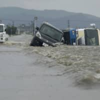 Cars are swept off a road Sunday morning after the Tachiarai River flooded due to typhoon-induced heavy rains in the town of Tachiarai, Fukuoka Prefecture. | KYODO