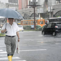 Pedestrians walk with umbrellas in the city center of Kagoshima on Wednesday as continuing torrential rain raises the risk of floods and mudslides. | KYODO