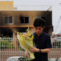 A man carries a bouquet of flowers as he prays for victims in front of the torched Kyoto Animation building in Kyoto on Saturday.  REUTERS | REUTERS