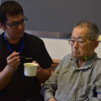 An elderly man tries out a Gokuri swallow analyzer in May in Tsukuba, Ibaraki Prefecture. When the device determines a patient has properly swallowed food, its light and a smartphone app flash green. | MASUMI KOIZUMI