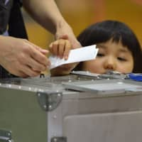 A girl watches as her mother casts her ballot in the Upper House election at a polling station in Tokyo on Sunday. | AFP-JIJI
