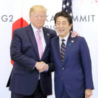 Prime Minister Shinzo Abe shakes hands with U.S. President Donald Trump in Osaka on June 28 during their meeting on the sidelines of a Group of 20 summit. | KYODO
