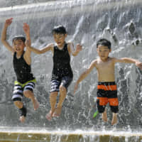 Children play at a fountain in a park in Tokyo's Edogawa Ward on Wednesday as a heat wave smothered wide swaths of the archipelago. | KYODO