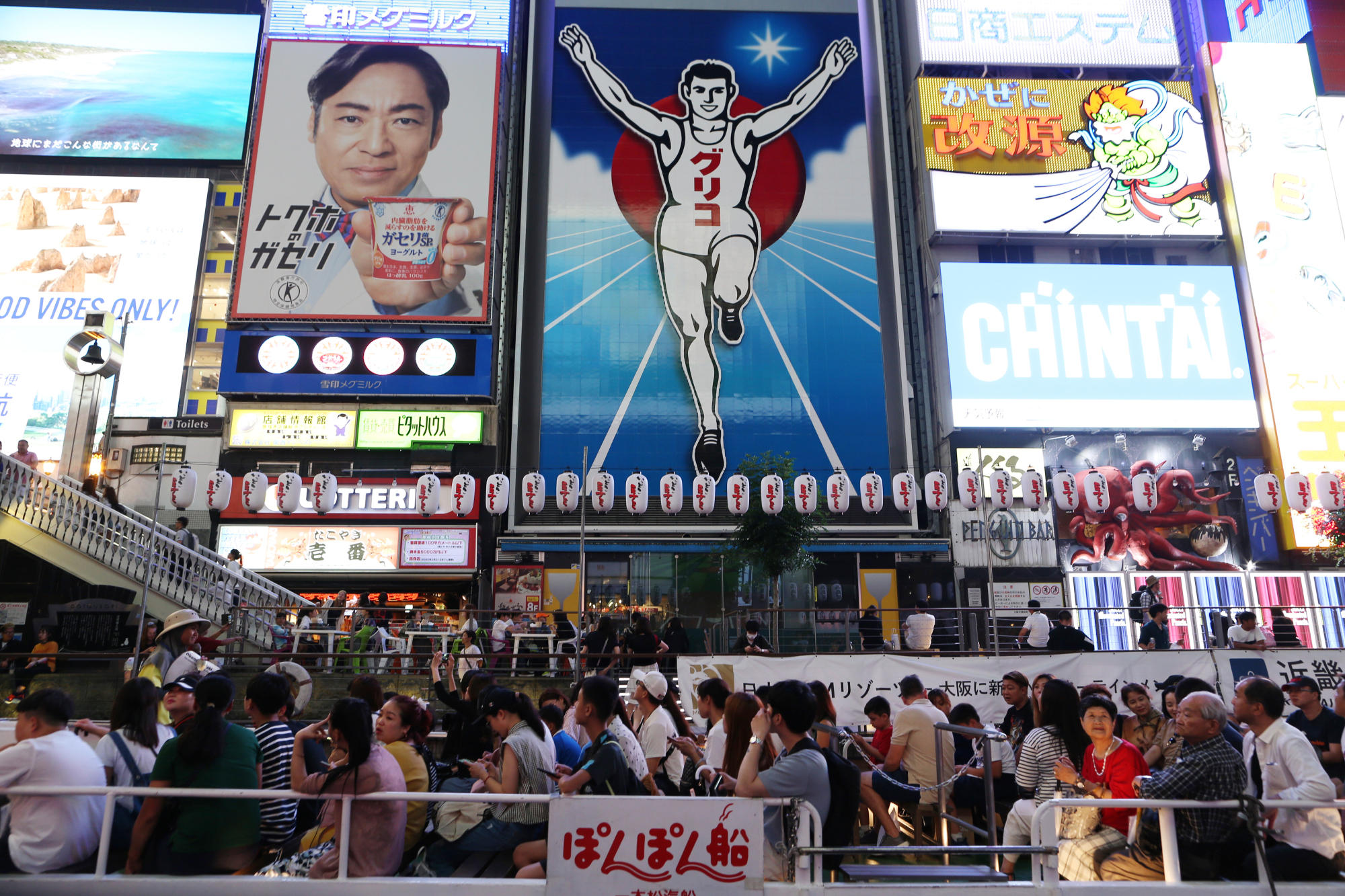 People walk around the Dotonbori downtown area of Osaka last month. Japan saw a record 16.63 million overseas visitors in the first six months of this year, according to government data released Wednesday. | BLOOMBERG
