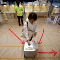 A voter casts her ballot at a voting station in Tokyo in Sunday's Upper House election. | REUTERS