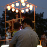 Quality time: A man and a young child take part in a summer festival. The Japanese government hopes the nation's fathers can take paternity leave. | KYODO