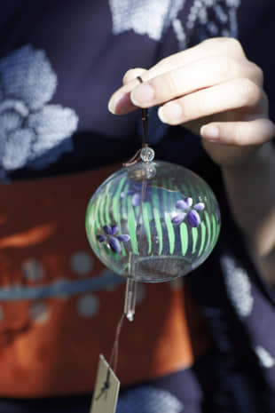 A woman holds a hand-made wind chime crafted by Shinohara Furinhonpo. The wind chime is still available from the manufacturer. | COURTESY OF KATEIGAHO INTERNATIONAL JAPAN EDITION