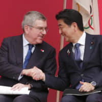 Prime Minister Shinzo Abe shakes hands with International Olympic Committee President Thomas Bach during the 'One Year to Go' Olympic ceremony event in Tokyo on Wednesday. | AP