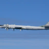 A Russian TU-95 bomber flies over the East China Sea in this picture taken by the Air Self-Defense Force and released by the Defense Ministry on Tuesday. | REUTERS