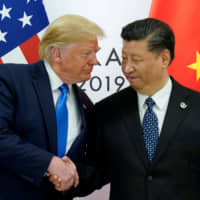 U.S. President Donald Trump greets Chinese President Xi Jinping at the start of their bilateral meeting at the G20 leaders summit in Osaka on Saturday. | REUTERS