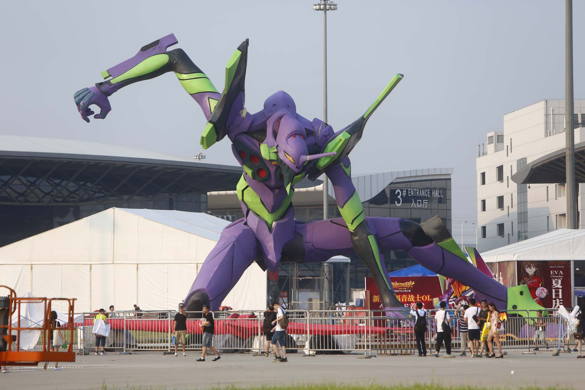 Visitors walk past a giant model of Evangelion Unit-01 from the 'Neon Genesis Evangelion' anime on display in Shanghai in June 2016. Japanese pop culture is thriving worldwide, but the Japanese entertainment industry could do much more to bring the profits back to Japan. | KE YI — IMAGINECHINA