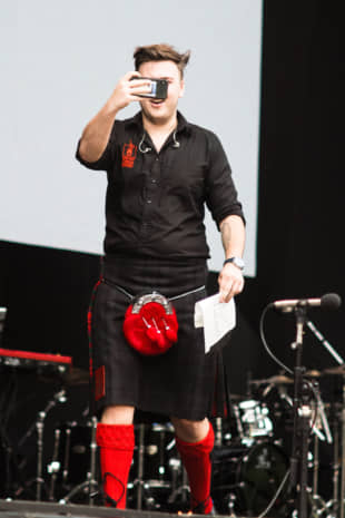 Happy snapper: One of the members of Red Hot Chilli Pipers captures the crowd.   RIKO MONMA