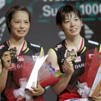 Yuki Fukushima (left) and Sayaka Hirota pose with their gold medals after defeating Misaki Matsutomo and Ayaka Takahashi in the women's doubles final match at the Indonesia Open badminton championship in Jakarta on Sunday. | AP
