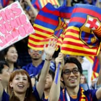 Barcelona fans show support for their team on Tuesday night. | REUTERS