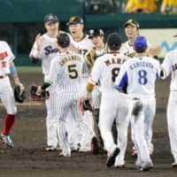 Central League All-Stars congratulate each other after their 11-3 victory over the Pacific League in Game 2 of the NPB All-Star Series on Saturday night at Koshien Stadium. | KYODO