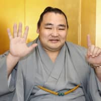 Yokozuna Kakuryu holds up six fingers to celebrate his sixth Emperor's Cup win during a Monday new conference in Nagoya. | KYODO