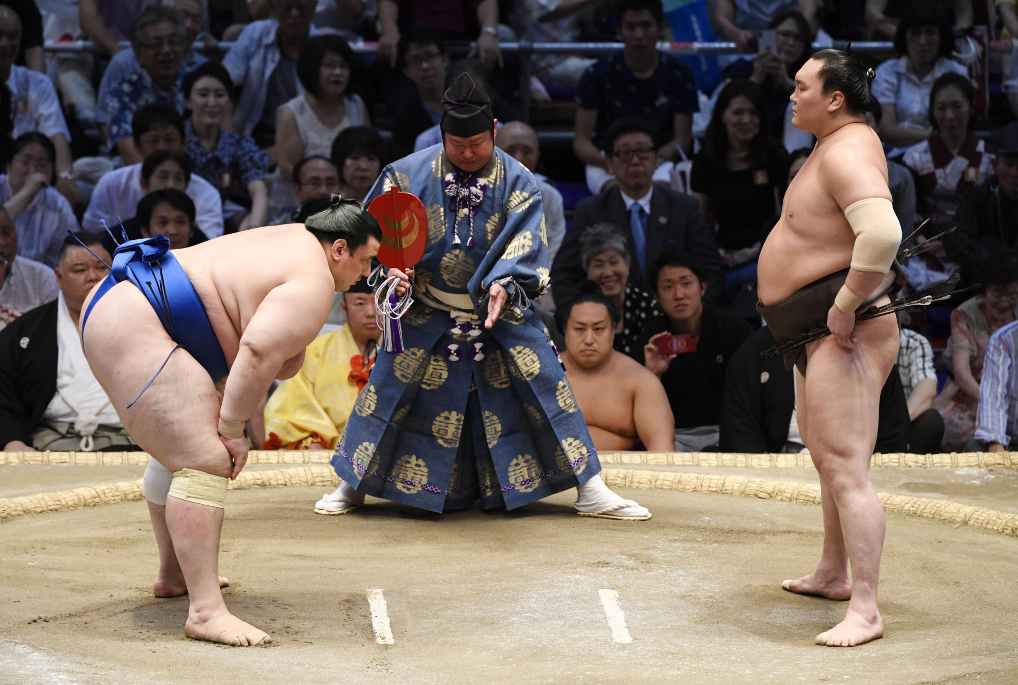 Yokozuna Hakuho (right) and maegashira Aoiyama stand behind the shikiri sen (the two white lines in the middle of the ring) before their bout on Friday in Nagoya. | KYODO