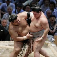 Takayasu (left) pushes Meisei out of the ring on Tuesday at Dolphins Arena in Nagoya during the 10th day of the Nagoya Grand Sumo Tournament. | KYODO