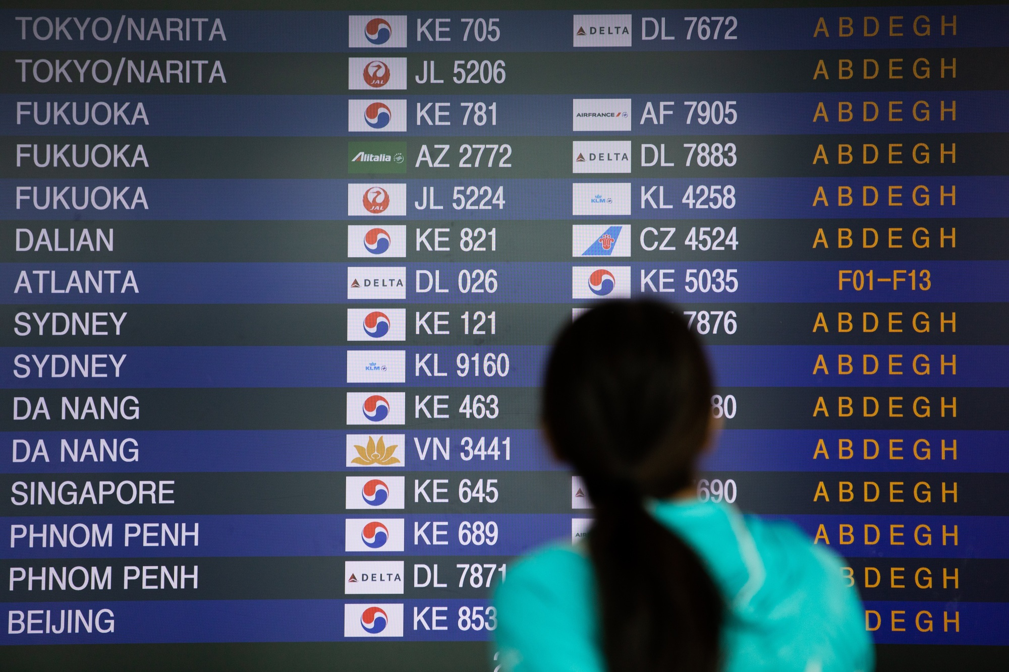 A passenger checks flight departure information at South Korea's Incheon International Airport on Aug. 7.   BLOOMBERG