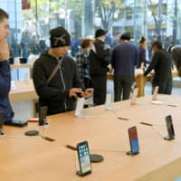 Browsers check out iPhones at the Apple store in Tokyo's Omotesando area in November 2017.   KYODO
