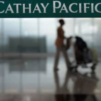 A woman walks past check-in counters for Hong Kong's flag carrier Cathay Pacific at Hong Kong's international airport in August 2014. Hong Kong's flag carrier Cathay Pacific has flown headlong into a political storm thrown up by the city's swirling pro-democracy protests, as Beijing turns the screws on any company deemed sympathetic to the movement. | AFP-JIJI