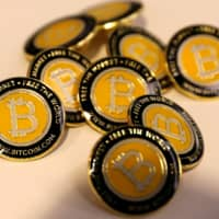 Bitcoin.com buttons are seen displayed on the floor of the Consensus 2018 blockchain technology conference in New York in May 2018. | REUTERS