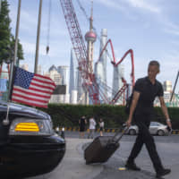 A traveller pulls his luggage past a U.S. Embassy car outside a hotel in Shanghai on July 30. China has announced it will raise tariffs on $75 billion of U.S. products in retaliation for President Donald Trump's planned Sept. 1 duty increase in a war over trade and technology policy. | AP