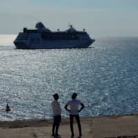 Men watch the cruise ship MS Empress of the Seas, operated by Royal Caribbean International, as it leaves the bay of Havana June 5. | REUTERS