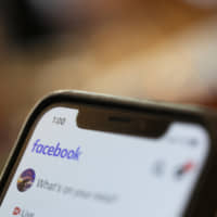 An iPhone displays a Facebook page Sunday in New Orleans. Facebook says it paid contractors to transcribe audio clips from users of its Messenger service.   AP