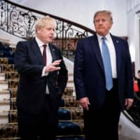 U.S. President Donald Trump and British Prime Minister Boris Johnson speak before a working breakfast at the Group of Seven summit in Biarritz, France, on Sunday. | POOL / VIA AFP-JIJI