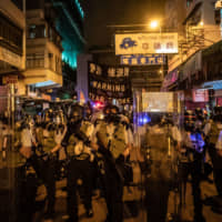 Police in the street prepare to charge protesters during a demonstration Wednesday in the Sham Shui Po district of Hong Kong. On the day, the city was marking the Hungry Ghost Festival, during which people pay homage to deceased ancestors. | GETTY IMAGES VIA BLOOMBERG