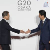 South Korean President Moon Jae-in greets Prime Minister Shinzo Abe prior to a photo session at the Group of 20 summit in Osaka on June 28. | BLOOMBERG