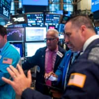 Wall Street traders work after the closing bell at the New York Stock Exchange on Monday. | AFP-JIJI