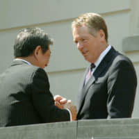U.S. Trade Representative Robert Lighthizer and economic revitalization minister Toshimitsu Motegi shake hands in front of the Office of the U.S. Trade Representative in Washington on Aug. 1.   KYODO