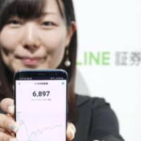A demonstration of Line Securities Corp.'s stock trading using a smartphone application is seen in Tokyo on Tuesday. | KYODO