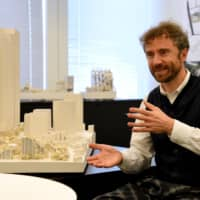British designer Thomas Heatherwick speaks alongside a miniaturized model of the Mori Building Co.'s new integrated development in the Toranomon-Azabudai area of Tokyo. | SATOKO KAWASAKI