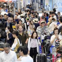 Travelers arrive at Narita Airport on Sunday after spending the Bon holidays overseas.   KYODO