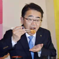 Aichi Prefectural Gov. Hideaki Ohmura eats miso cutlet, a speciality from Nagoya, in March in an attempt to show the safety of locally produced pork.   KYODO