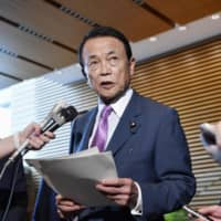 Finance Minister Taro Aso speaks to reporters last week at the Prime Minister's Office in Tokyo. | KYODO