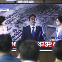 People watch a TV program showing an image of Prime Minister Shinzo Abe, at Seoul Station on Friday. Japan has approved the removal of South Korea from a 'white list' of countries with preferential trade status, escalating tensions between the neighbors. | AP