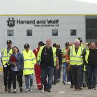 Harland and Wolff shipyard workers emerge after voting to continue their occupation of the shipyard, in Belfast Monday.   LIAM MCBURNEY / PA / VIA AP