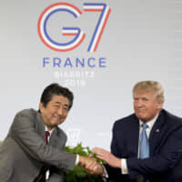 Prime Minister Shinzo Abe and U.S. President Donald Trump shake hands during their bilateral meeting on the sidelines of the Group of Seven summit in Biarritz, France, on Sunday. | AP