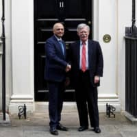 British Chancellor of the Exchequer Sajid Javid (left) shakes hands with U.S. National Security Adviser John Bolton at Downing Street in London Tuesday. | REUTERS