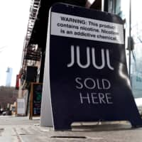 A sign advertising Juul brand vaping products is seen outside a shop in Manhattan in New York City in February. | REUTERS