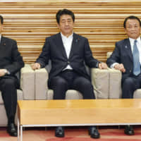 Prime Minister Shinzo Abe attends a Cabinet meeting with Finance Minister Taro Aso (right) and Land, Infrastructure, Transport and Tourism Minister Keiichi Ishii and others at Abe's official residence in Tokyo on Friday. | KYODO