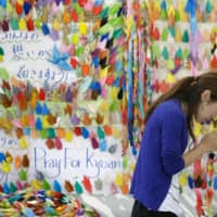 Thoughts and prayers: A woman prays at an altar set up for victims of the arson attack on Kyoto Animation's main studio. Fifty-thousand paper cranes have been placed at the altar. | KYODO