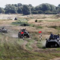 Armored personnel carriers compete during the International Army Games 2019 at the Khmelevka firing ground on the Baltic Sea coast in Kaliningrad Region, Russia, Tuesday. | REUTERS